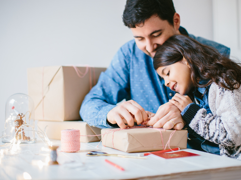 Father and daughter wrapping gifts together at a table