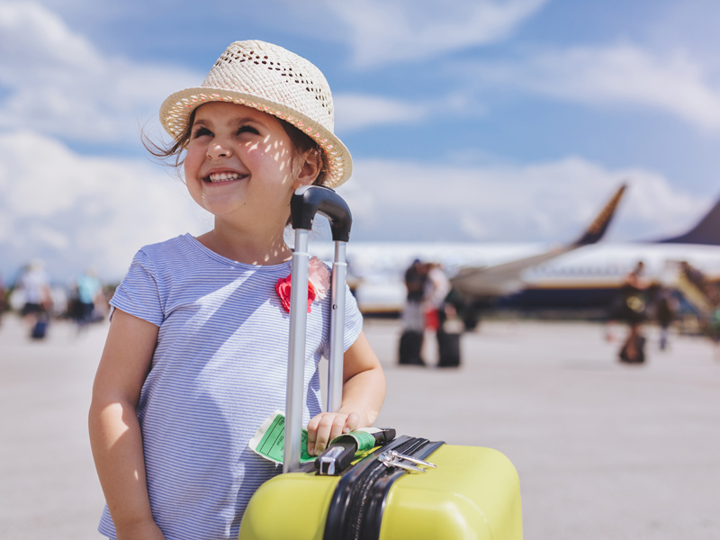 Smiling child with suitcase standing beside an aeroplane