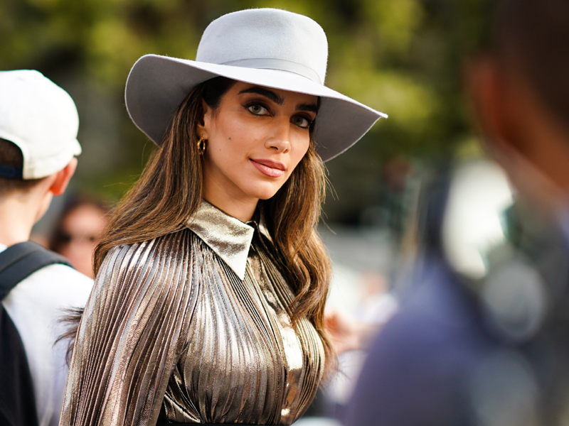 Model and influencer Jessica Kahawaty wearing a gold shirt and hat at Fashion Week