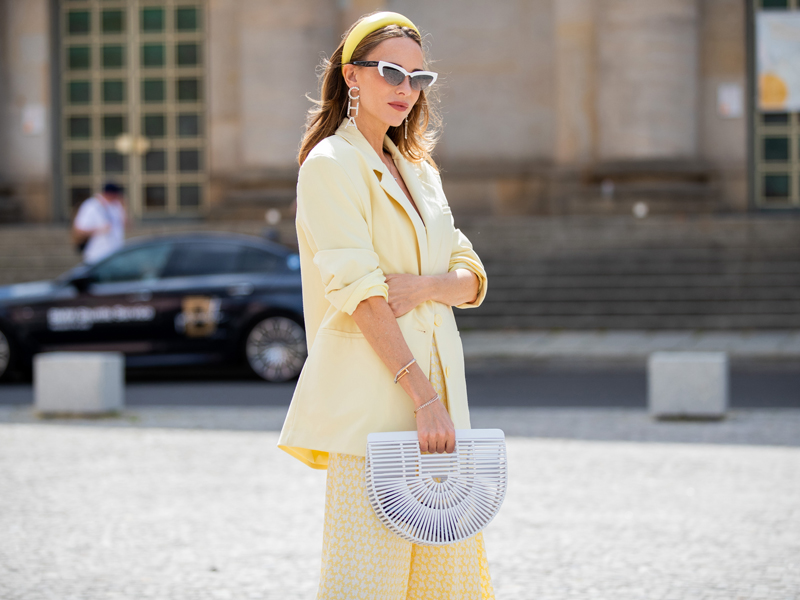 A fashionably dressed woman wearing a lemon suit with a ladies' bag in a street style photo
