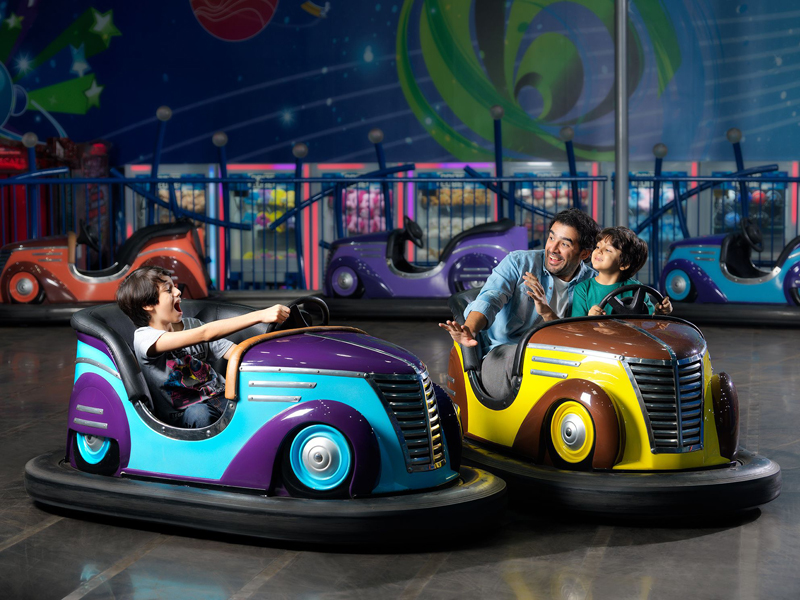 A father and his kids playing on bumper cars at Magic Planet in Bahrain