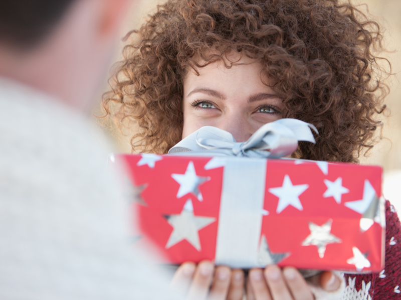 Woman with curly hair holding gift-wrapped present