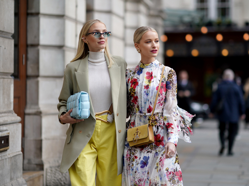 Two stylish women carry in a street scene